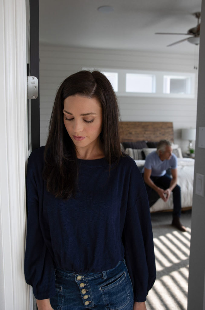 woman in foreground looks down sadly as husband sits on bed